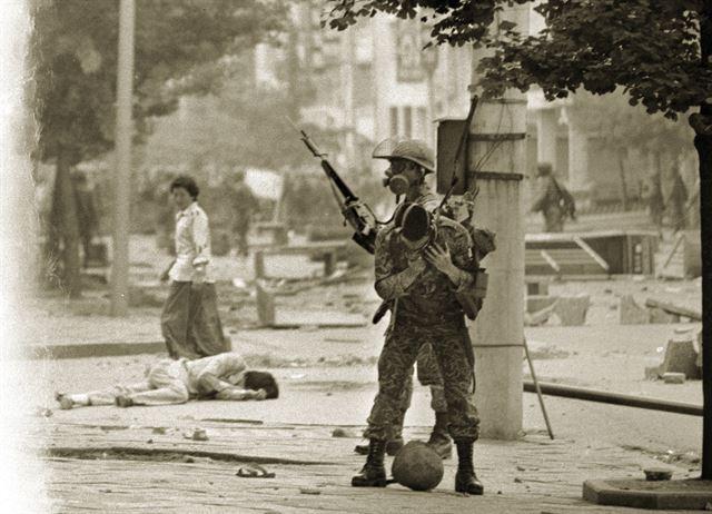한바탕 투석전이 벌어진 거리에서 한 청년이 나뒹굴고 있다. 주변 계엄군의 서슬에 겁을 먹은 여성은 그를 도울 수도 지나칠 수도 없다. 불과 몇 m 떨어지지 않은 곳에선 계엄군이 철모를 내려놓고 방독면을 고쳐 쓰고 있다. 무자비한 진압작전은 그 후로도 계속됐다. 1980년 5월 20일 전남 광주시 금남로.
