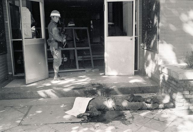 저항의 끝은 처절한 죽음이었다. 27일 오전 전남도청 진압작전에 나선 계엄군이 사살된 시민군의 주검을 무표정하게 바라보고 있다.