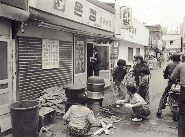 5월 20일 금남로에서 치열한 투석전이 벌어지는 동안 골목 식당 앞에선 시민들이 큰 솥을 걸고 시민군에게 줄 주먹밥을 만들고 있다.