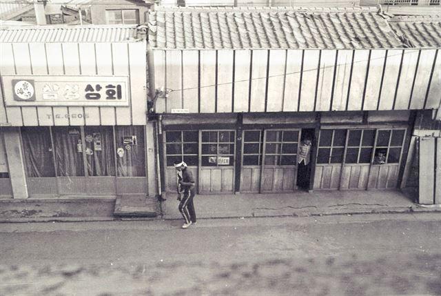 21일 광주 시내 한 골목길에서 간헐적인 시가전이 벌어지고 있는 동안 어린 아이가 창문 틈으로 이를 구경하고 있다.