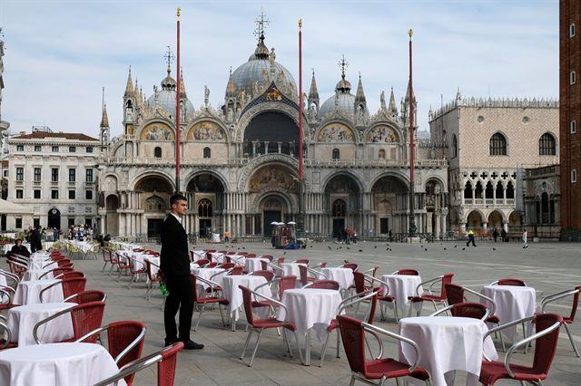 9일 이탈리아 베니스 산 마르코 광장 인근에 위치한 한 레스토랑에서 직원이 텅 빈 테이블을 바라보고 있다. 베니스=로이터 연합뉴스