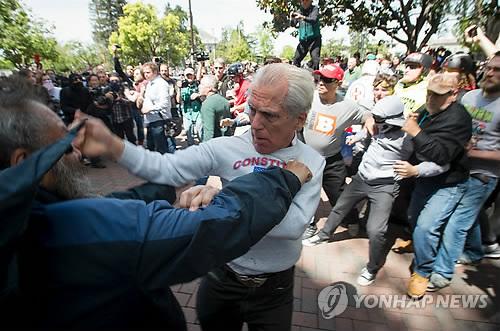 (버클리 AFP=연합뉴스) 지난 15일 미국 캘리포니아주 버클리에서 도널드 트럼프 대통령의 납세내용 공개를 촉구하는 시위대와 트럼프 대통령 지지자들이 충돌, 유혈사태로까지 이어진 가운데 두 남자가 격렬한 싸움을 벌이고 있다.