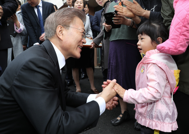 문재인 대통령이 5월10일 오전 현충원 참배를 위해 서울 홍은동 자택을 나서며 어린아이의 손을 잡고 대화하고 있다. 연합뉴스