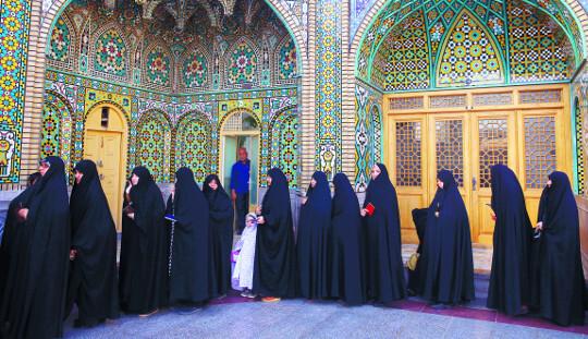 이란 대통령 선거와 지방의회 의원 선거가 동시에 실시된 19일(현지시간) 차도르를 입은 이란 여성 유권자들이 수도 테헤란 남부도시 쿰의 투표소에서 투표하기 위해 줄지어 기다리고 있다. 투표 결과는 20일 새벽에 나온다.   AP뉴시스