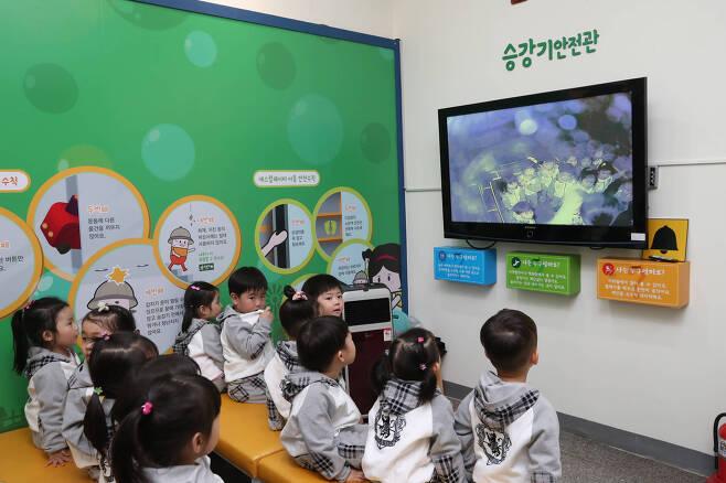어린이들이 1층 승강기안전관에서 승강기가 멈췄을 때의 행동요령 체험을 하고 있는 친구들을 모니터를 통해 바라보고 있다. 우상조 기자
