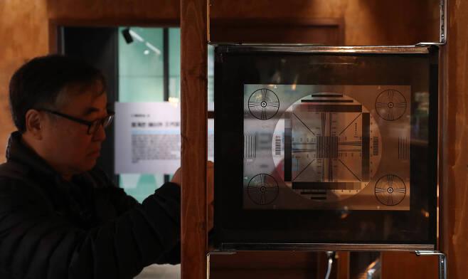 전시장을 찾은 관람객이 화면 조정판 건너편으로 전시품 사진을 찍고 있다. 우상조 기자