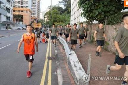 홍콩 거리에서 청소 작업을 벌이는 중국군에 포함된 대테러 특수부대원(왼쪽) [AFP통신=연합뉴스]