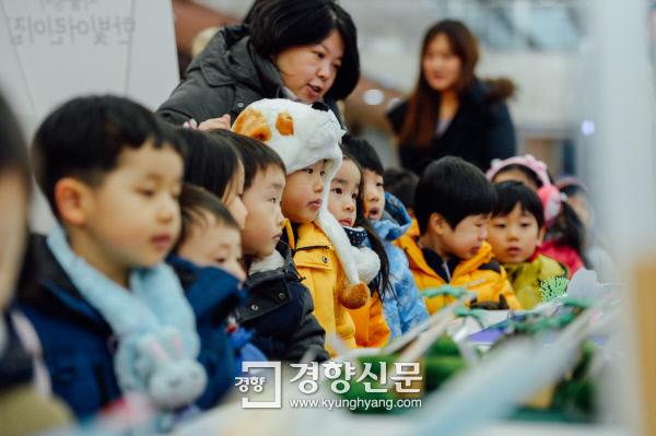 정부서울청사 한빛어린이집 원생들이 19일 어린이작품 전시회가 열리고 있는 청사 1층 로비에서 또래들이 그린 그림 등을 구경하고 있다. 이준헌 기자