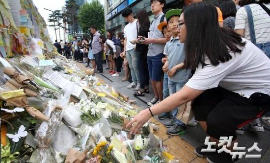 21일 오후 '강남 묻지마 살인' 추모현장인 강남역 10번 출구를 찾은 시민들이 추모의 글을 적은 메모지를 붙이고 헌화를 하고 있다. (사진=황진환 기자)