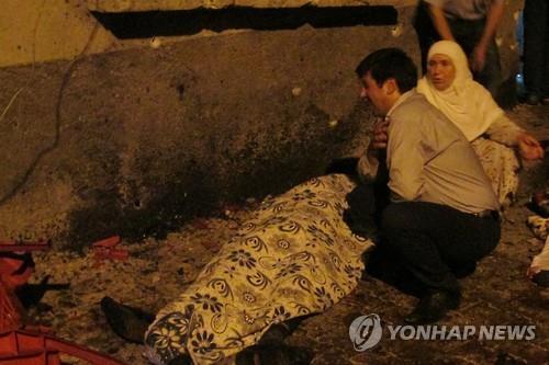 한 남성이 결혼식장 테러 현장의 시신 옆에서 울고 있다 [AP=연합뉴스]