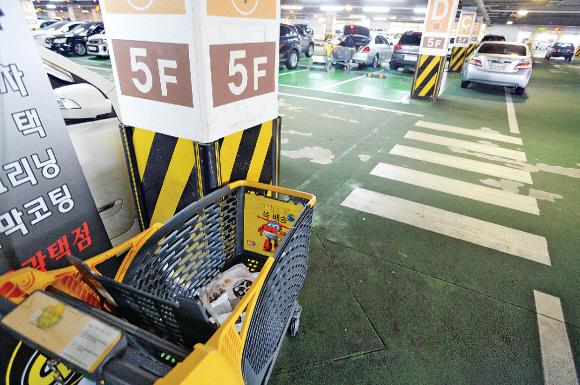 7일 서울 성동구 성수동에 있는 이마트 주차장 구석에 플라스틱 카트가 내팽개쳐져 있다. 카트 안에는 장을 보면서 남긴 쓰레기가 그대로 담겨 있다.이언탁 기자 utl@seoul.co.kr