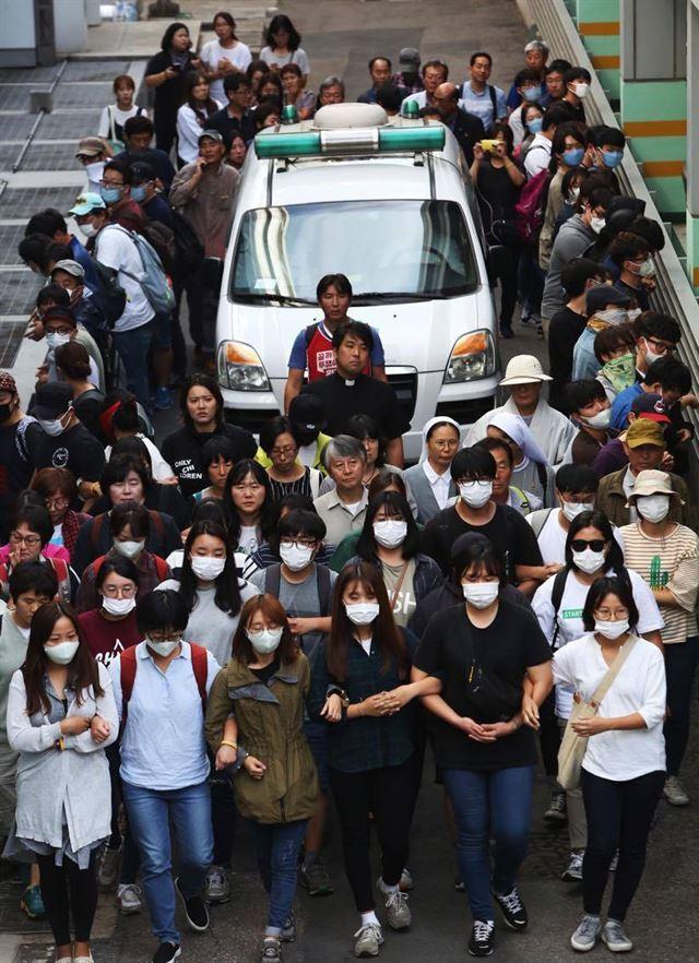 지난달 25일 백남기의 시신을 지키기 위해 운구차 옆에 늘어선 시위대. 권력은 이들을 향해 당당하다면 얼굴을 드러내라고 한다. 오마이뉴스 제공