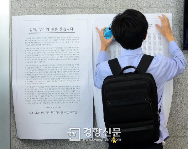 한양대 의과대학생이 서울대병원 장례식장 입구에 전국 의과대학 809명의 연명이 담긴 성명서를 부착하고 있다. / 김창길 기자
