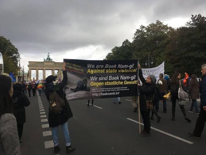 8일 독일 베를린에서 열린 반전 시위에 한국 교민들이 '우리는 백남기(농민)에 대한 국가폭력을 반대한다'고 적힌 팻말을 펼쳐 보이고 있다. 한주연 통신원