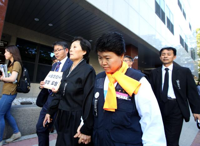 10월4일 고 백남기씨의 부인 박순례씨(가운데)가 '병사'로 기재된 사망진단서의 정정을 요청하는 문서를 접수하기 위해 이동하고 있다. 정용일 기자