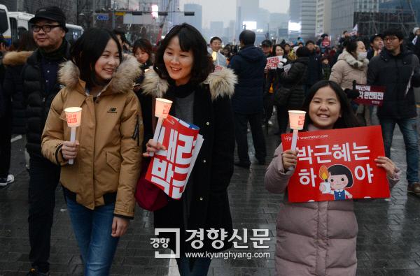 박근혜정권 퇴진을 위한 5차 촛불집회가 열린 11월 26일 서울 광화문광장에서 한 가족이 촛불을 들고 행진하고 있다. / 서성일 기자