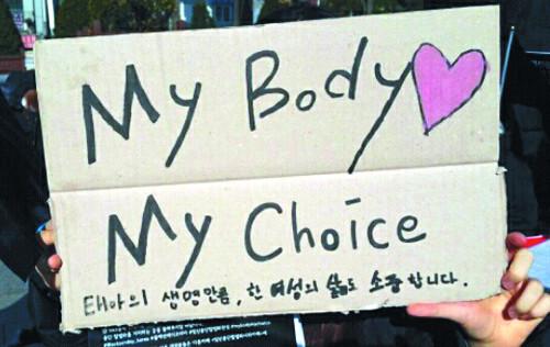 """한 여성단체 회원이 """"낙태수술을 불법으로 규정하는 것은 여성의 인생에도 영향을 줄 수 있는 문제""""라며 시위를 벌이고 있다."""