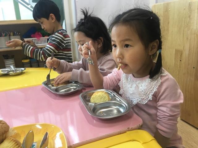 지난달 28일 경기 군포의 이주아동 어린이집에서 아이들이 점심을 먹기 전 식사예절 관련 노래영상을 보고 있다.