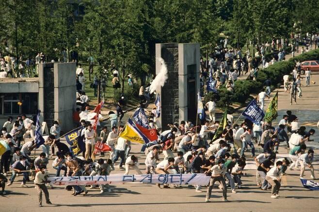1987년 6월9일 서울 연세대학교 앞에서 이한열 열사가 피격되기 직전의 모습. 왼쪽 흰 현수막 뒤에 영문자로 '연세'라고 쓰인 티셔츠를 입고, 파란색 마스크를 쓰고 있는 이한열 열사의 모습이 보인다. 네이선 벤 제공