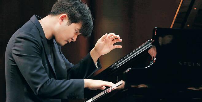 건반과 씨름하는 이 청년의 눈빛이 뜨겁다. 지난 9일 오후(현지 시각) 미 텍사스주 포트워스의 베이스 퍼포먼스 홀에서 반 클라이번 콩쿠르의 결승 무대에 선 선우예권은 러시아의 작곡가 라흐마니노프가 스스로의 한계를 뛰어넘고자 쓴 피아노 협주곡 3번을 소화해 당당히 우승을 거머쥐었다. /반 클라이번 콩쿠르