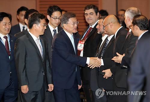 (제주=연합뉴스) 배재만 기자 = 문재인 대통령이 16일 오후 제주 국제컨벤션센터에서 열린 '아시아인프라투자은행(AIIB) 연차총회'에서 참석자들과 악수하고 있다.       scoop@yna.co.kr