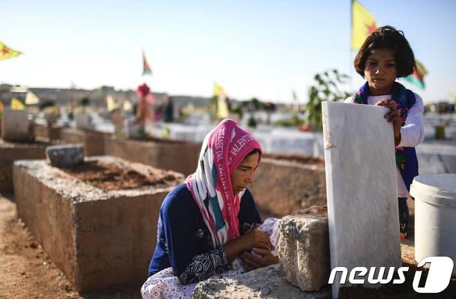 한 시리아 여성이 숨진 남편의 묘를 살피고 있다. © AFP=뉴스1
