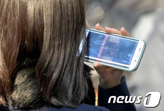 스마트폰을 이용해 동영상을 감상하고 있는 시민의 모습/뉴스1 © News1