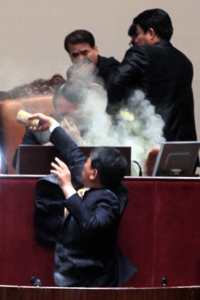 2011년 11월22일 김선동 민주노동당 의원이 국회 본회의장에서 한나라당(자유한국당의 전신)이 단독으로 한-미 자유무역협정(FTA) 비준동의안 처리를 강행하려 하자 최루탄을 터뜨린 뒤 정의화 당시 국회부의장이 있는 의장석에 최루가루를 뿌리고 있다. 정 당시 국회부의장은 최루가루를 털어낸 뒤 자리를 정돈하고 본회의를 열어 에프티에이 비준안 및 관련 법안을 처리했다. 노컷뉴스 제공