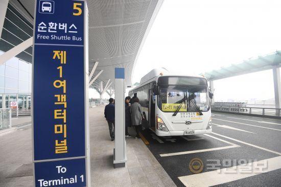 T2에서 T1으로 가는 셔틀버스 타는 승객들.