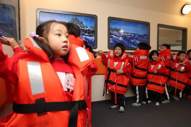 3층 선박안전체험관의 안전호에 올라탄 어린이들이 흔들리는 배안에서 난간 손잡이를 붙잡고 있다. 양손으로 손잡이를 붙잡고 있는 어린이, 장난스럽게 웃고 있는 어린이, 긴장한 듯 경직된 어린이 등 저마다 표정이 다양하다. 우상조 기자