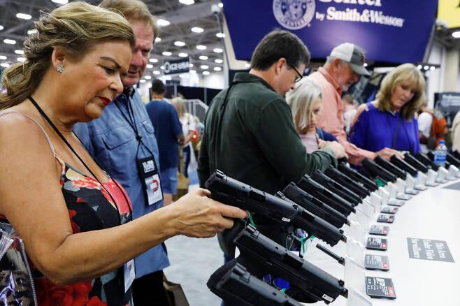 사람들이 소형 권총을 만져보고 있다. [로이터=연합뉴스]