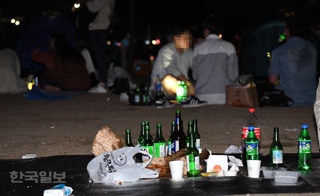 지난 21일 오후 서울 영등포구 여의도한강공원에서 시민들이 술을 즐기고 있는 가운데, 누군가 치우지 않고 떠난 자리에 술병과 음식 쓰레기 등이 뒹굴고 있다. 배우한 기자