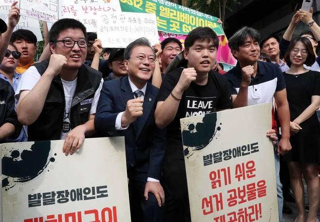 문재인 대통령이 8일 서울 종로구 삼청동주민센터에서 사전 투표를 한뒤 참정권을 보장시위를 하는 장애인단체와 기념사진을 찍고 있다. 청와대사진기지단