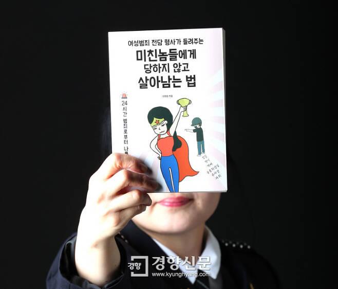 <미친놈들에게 당하지 않고 살아남는 법>을 쓴 13년차 여성 경찰 이회림 경사(필명)가 지난 9일 경향신문에서 자신의 책을 들어 보이고 있다. 정지윤 기자