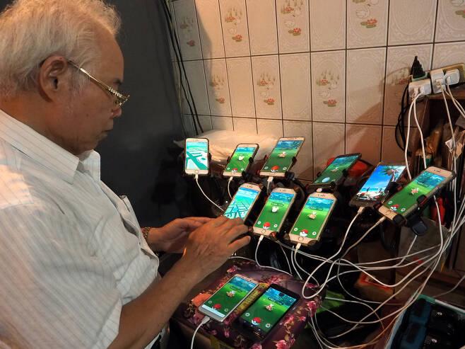 풍수 전문가 첸 산 위안이 8일(현지시간) 대만 신베이시에서 자신의 11대의 스마트폰을 충전하고 있다.[EPA=연합뉴스]