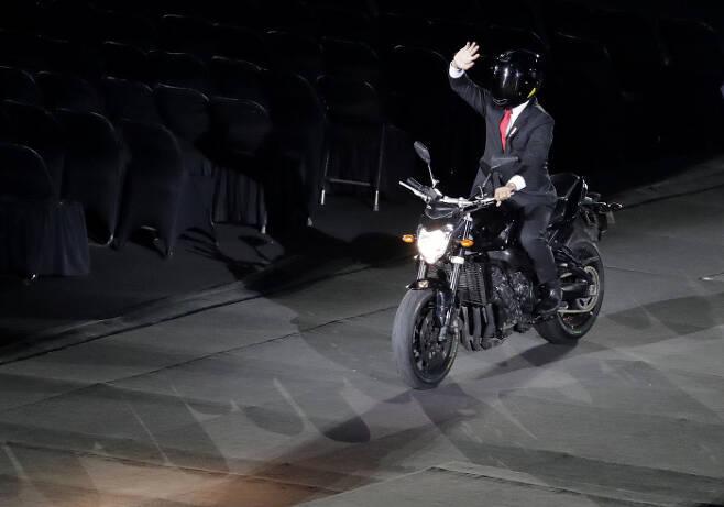 인도네시아 조코 위도도 대통령이 아시안게임 개막식 때 오토바이를 타고 나타나 팬들의 환호에 손을 흔들어 답하고 있다. | AP연합뉴스