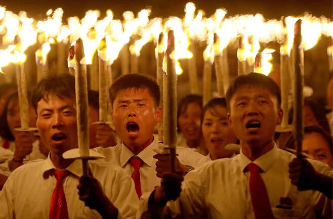 횃불을 든 북한 청년들이 10일 오후 평야 김일성광장에서 정권수립 70주년을 축하하며 퍼레이드를 하고 있다. [타스=연합뉴스]