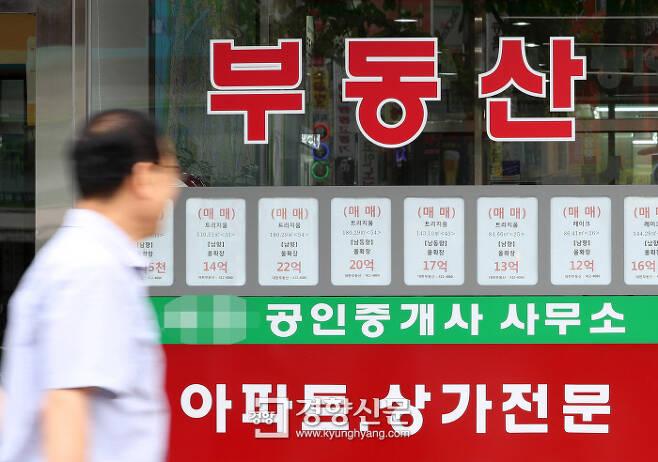 14일 한 시민이 매매가 10억원대 매물정보가 게시된 서울시내 공인중개사사무소 밀집상가를 지나가고 있다. 김창길 기자 cut@kyunghyang.com