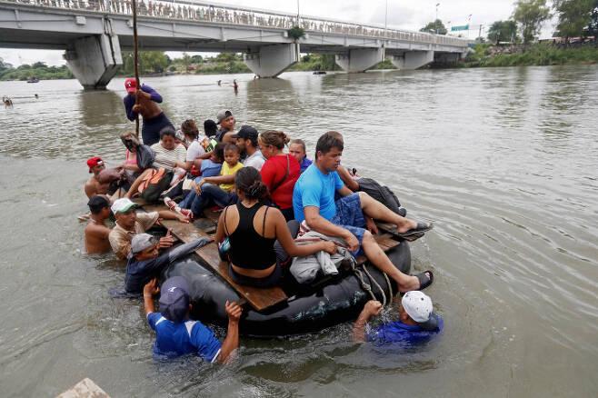 온두라스 이민자들이 멕시코 국경을 넘기 위해 수치아떼 강을 튜브를 이용한 배로 넘고 있다. EPA=연합뉴스