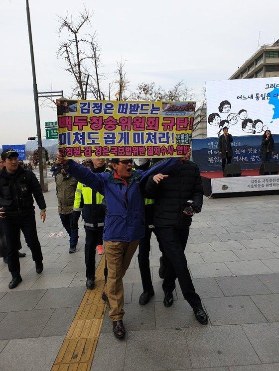 홍정식 활빈단 대표가 18일 백두칭송위원회의 연설대회 '김정은' 시작 전 행사 중단을 요구하며 항의시위를 하고 있다. 김다영 기자