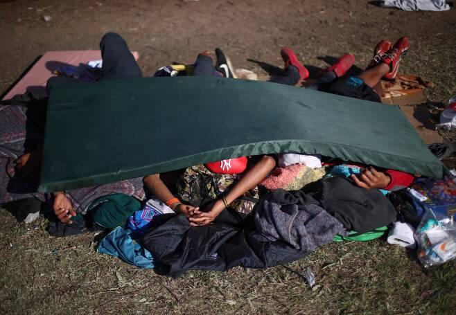 캐러밴 이민자들이 18일(현지시간) 멕시코 티후아나 시 임시 보호소 땅 바닥에서 잠을 자고 있다. [로이터=연합뉴스]