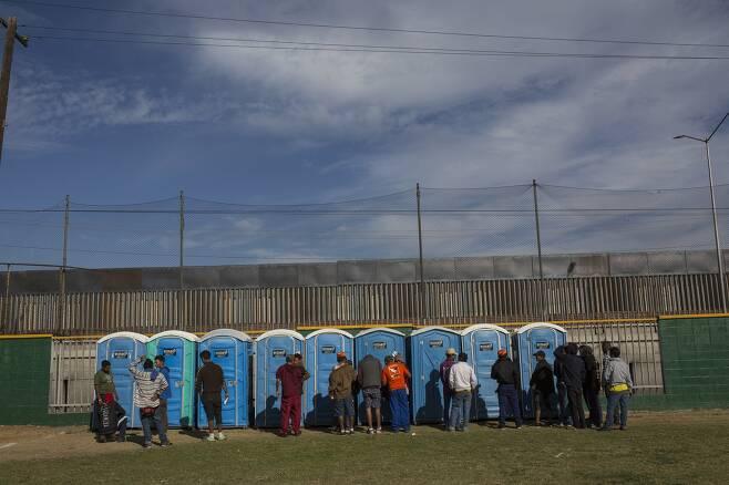 캐러밴 이민자들이 18일(현지시간) 멕시코 티후아나 시 임시 보호소에서 화장실 앞에 줄을 서 있다.[AP=연합뉴스]