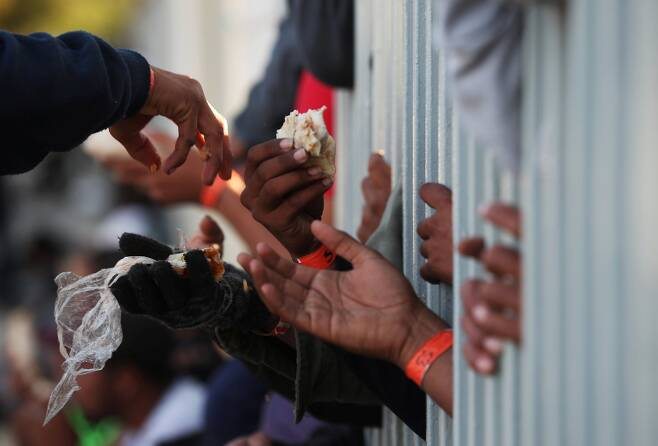 캐러밴 이민자들이 18일(현지시간) 멕시코 티후아나 임시 보호소에서 음식을 받고 있다. [로이터=연합뉴스]
