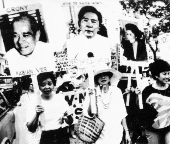 1986년 필리핀 시민들이 마르코스 대통령과 부인 이멜다의 초상화를 들고 시위를 하고 있다. [중앙포토]