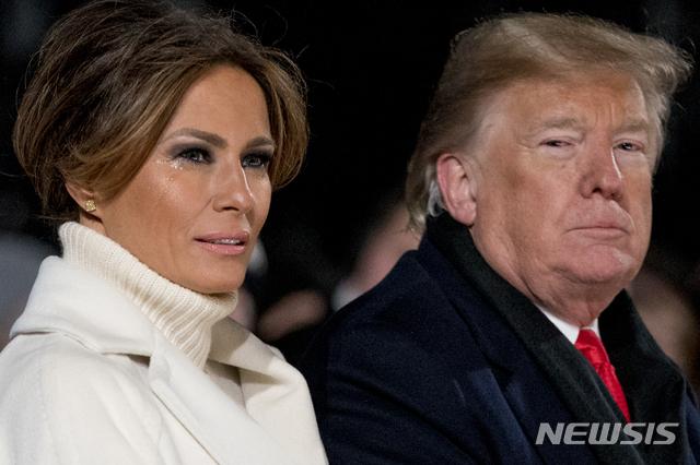 【워싱턴DC=AP/뉴시스】도널드 트럼프(오른쪽) 미국 대통령과 아내 멜라니아 트럼프가 28일(현지시간) 백악관 근처 일립스(프레지던트파크 사우스)에서 열린 제96회 내셔널 크리스마스트리 점등식에 참석한 가운데 때마침 불어온 강한 찬바람에 멜라니아 트럼프의 눈가에 눈물이 맺혀있다. 이 점등식은 제30대 대통령인 캘빈 쿨리지가 1923년 크리스마스이브에 처음으로 '내셔널 크리스마스트리'를 세우면서 시작돼 워싱턴 최고의 크리스마스 전통으로 이어지고 있다.2018.11.29.