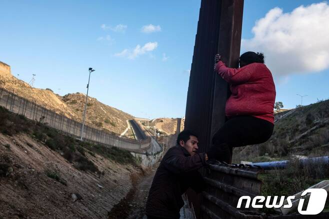 지난달 27일(현지시간) 중미 이민자 2명이 멕시코 티후아나와 미국 샌디에이고 국경지대를 넘고 있다. © AFP=뉴스1