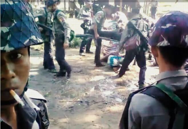 2016년 11월5일 미얀마 무장경찰들이 미얀마 서부 라카인주 북쪽의 로힝야 거주지 쿠텐콱 마을에서 남성 주민들을 한곳에 앉혀놓고 발길질하고 있다. 2017년 8월 집단학살이 벌어지기 전에도 미얀마 정부의 탄압은 일상적으로 벌어졌다. 이 영상은 한 무장경찰이 이 장면을 배경으로 자신의 모습을 촬영한 것이다.   유튜브 캡처