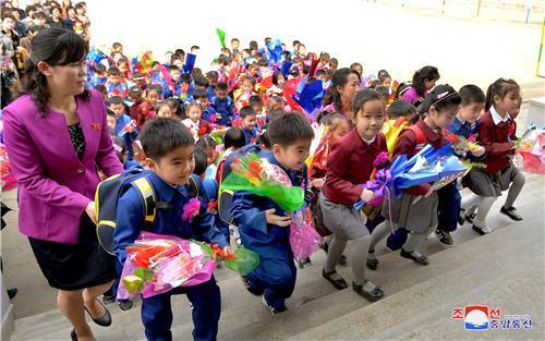 (평양 조선중앙통신=연합뉴스) 2018년 4월 3일 북한 평양 시내 한 소학교 입학식에서 꽃다발을 든 신입생들이 선생님과 함께 교실로 향하고 있다.