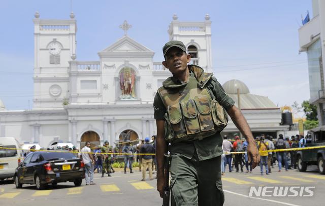 【콜롬보(스리랑카)=AP/뉴시스】21일(현지시간) 스리랑카 콜롬보의 성 안소니 사원 앞에서 한 경찰관이 주변을 통제하고 있다.  스리랑카 경찰은 전날 교회와 호텔 등 섬 전역에 걸쳐 228명의 사망자를 낸 8건의 연쇄 폭발 용의자 13명을 체포했다고 22일 밝혔다. 2019.04.22.