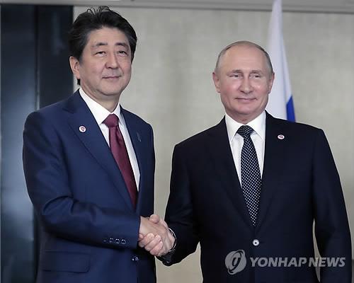 아베 신조 일본 총리(왼쪽)와 블라디미르 푸틴 러시아 대통령이 작년 11월 싱가포르에서 만나 악수를 나누는 모습 [EPA=연합뉴스 자료사진]